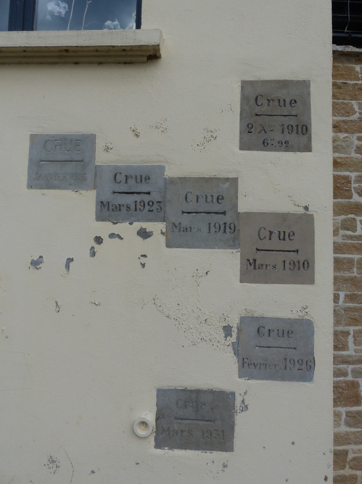 Flood markers on the wall of a house beside the river