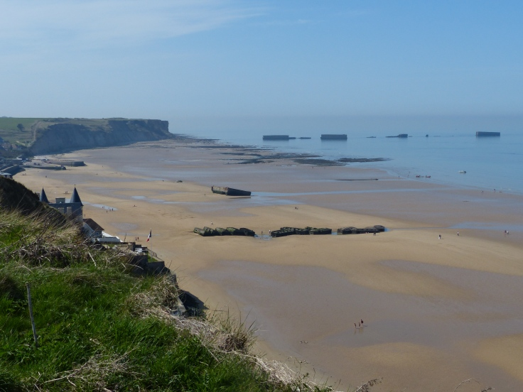 Gold Beach with remains of the floating harbour in the background