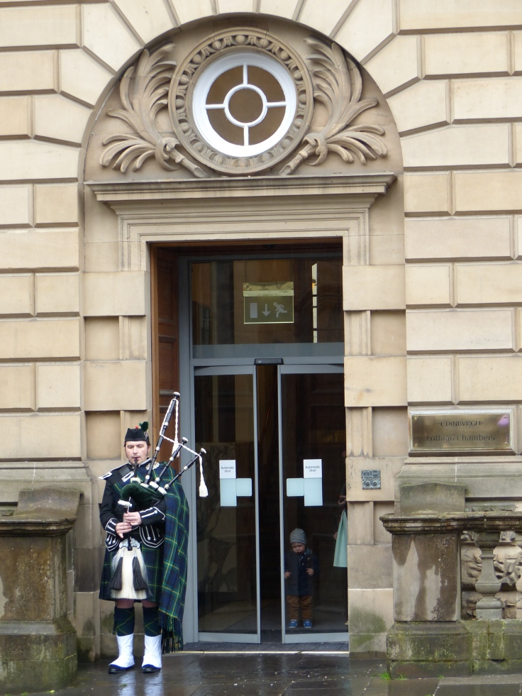 The piper outside the parliament building in the Royal Mile